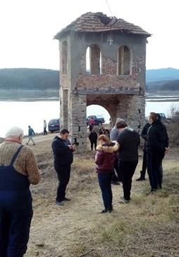 Хора се удивляват на изплувалата камбанария.