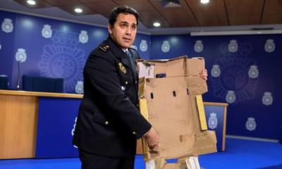 Испански полицай показва един от кашоните с лайм, в който е крита дрога.