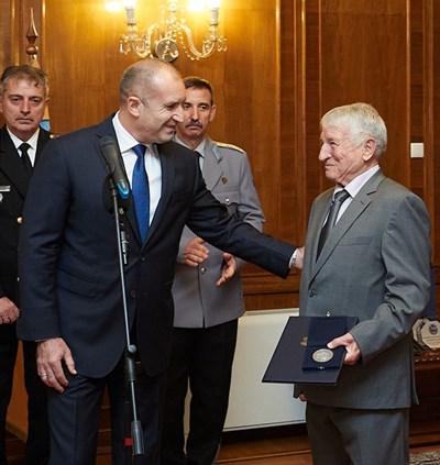 """В деня на ВВС Румен Радев удостои с Почетния знак на президента о.з. полк. Цветан Доганов по случай 60 г. от началото на неговата летателна дейност. """"Полк. Доганов е прекрасен инструктор, владеещ до съвършенство и теорията, и практиката, и """"душата"""" на полета"""", каза той и му пожела да продължава да е вдъхновител на младите. СНИМКА: Снимка: Пресслужба На Президента"""