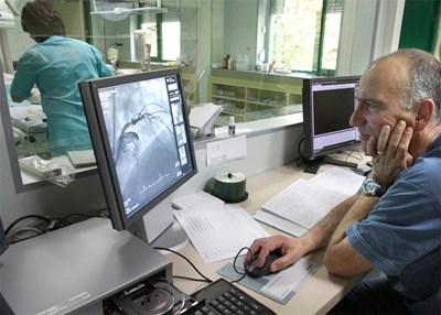 Д-р Хазърбасанов гледа резултатите от изследване на пациент. СНИМКА: Пиeр Пeтров
