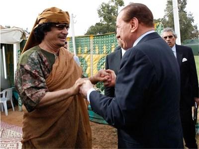Силвио Берлускони се здрависва с Муамар Кадафи в Триполи. Веднага след визитата си в София италианският премиер отлетя за Либия. Часове по-рано джамахирията пусна у дома швейцарския бизнесмен Макс Гьолди, който прекара известно време в затвора по обвинение в нелегално пребиваване на територията на страната. СНИМКА: РОЙТЕРС