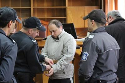 """Служители на """"Съдебна охрана"""" отвеждат в линейката колабиралия в съдебната зала Христо Спасов."""