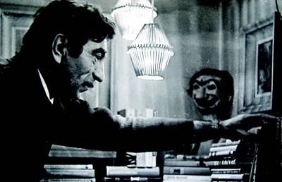 Георги Парцалев у дома сред книгите си. В дъното се вижда неговата маска