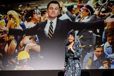Участничка в социалната програма See It Be It говори пред аудиторията на фона на плакат на Леонардо ди Каприо.