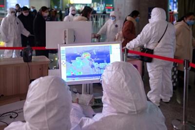 Служители сканират температурата на пътниците, пристигащи на гарата в китайския град  Нанцзин, за да  търсят заразени с коронавируса.