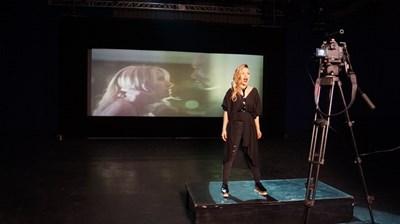 """Кадър от клипа на песента на Поли Генова за Евровизия. На заден план се вижда екрана със сцена от """"Под прикритие"""".  СНИМКА: БНТ"""