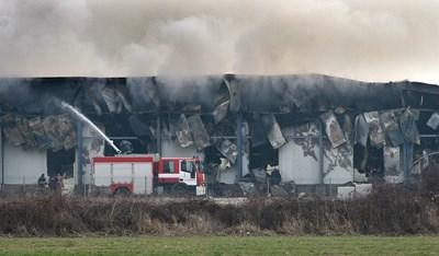 Пожарни обливат с вода тлеещите огнища в завода. СНИМКА: Евгени Цветков