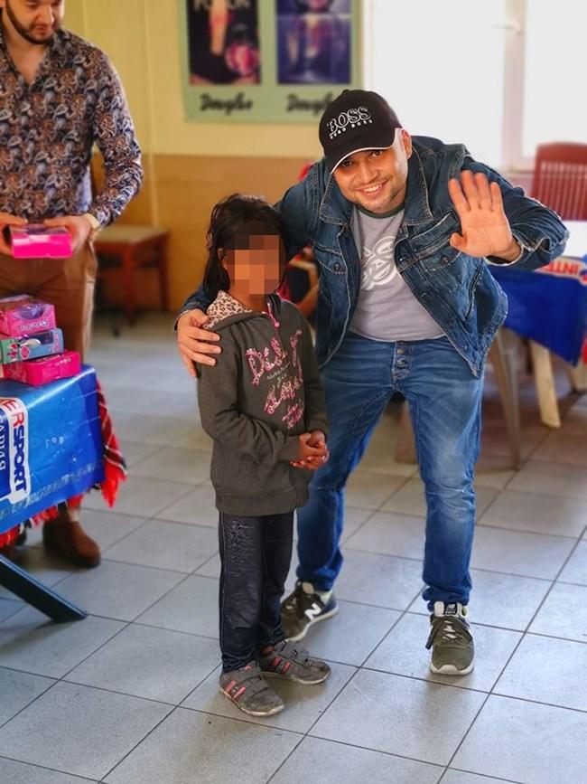 Йоско Алипиев с едно от 30-те деца, които получиха коледни подаръци тази година.