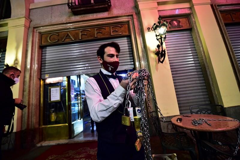 Келнер затваря кафене в Торино след въвеждането на нови ограничителни мерки в Италия.