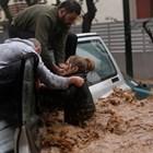 Спасители помагат на пострадала жена от бурята в Гърция.