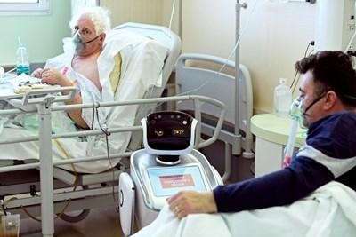 Робот помага на медицинския персонал при грижата за пациентите в болница във Варезе, Италия  Снимка: Ройтерс