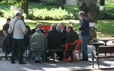 Група мъже играят карти в Цар-Симеоновата градинка, малко от тях са с маски.