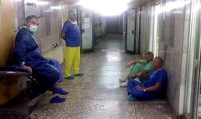 На пода седнал е проф. Венцислав Мутафчийски, до него д-р Бърдаров, срещу тях изправеният лекар е д-р Магаев. Седналият на носилката, е проф. Николай Младенов, а до него е проф. Асен Балтов, на когото му се вижда само кракът.