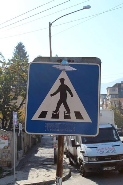 Първият пътен знак, който претворява уличният артист, е на пешеходец с НЛО.