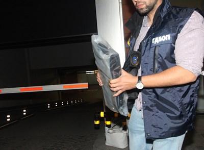 """Полицай изнася един от компютрите, за които се твърди, че са ползвани за хакерската атака срещу НАП.  СНИМКИ: """"24 ЧАСА"""""""