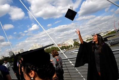 Студенти от Юнивърсити Колидж Лъндън празнуват с приятели и роднини дипломирането си на церемония в Саутбенк, Лондон.  СНИМКА: РОЙТЕРС