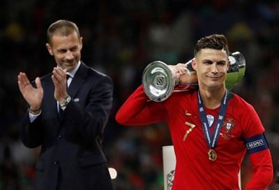 Звездата на Португалия Кристиано Роналдо е понесъл през рамо купата на Лигата на нациите пред одобрителния поглед на президента на УЕФА Александър Чеферин. СНИМКА: РОЙТЕРС