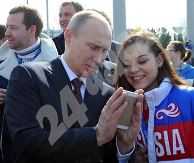 Владимир Путин разглежда айфона на своя почитателка. Кремълският бос твърди, че няма мобилен.
