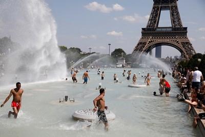 Десетки парижани се разхлаждат във фонтаните пред Айфеловата кула, след като жегата надхвърли 40°. В Южна Франция в петък се очакват 45°, което ще е нов национален рекорд за юни. СНИМКА: РОЙТЕРС