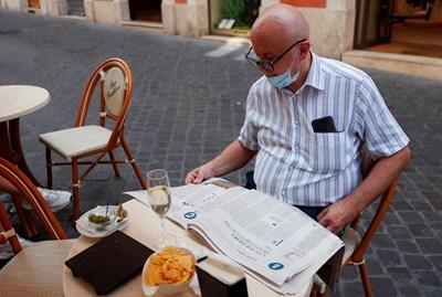 Италианец чете вестник, за да следи развитието на пандемията.