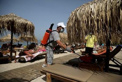 Служител дезинфекцира шезлонг на плаж край Атина. СНИМКА: РОЙТЕРС