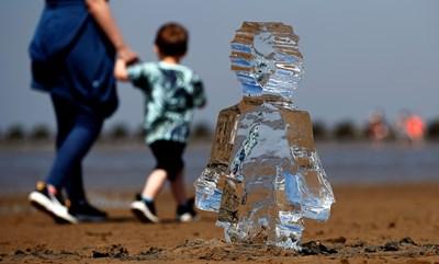 Ледена скулптура на дете, поставена на плаж във Великобритания, подчертава нуждата от спешни действия за изменението на климата. СНИМКА: РОЙТЕРС