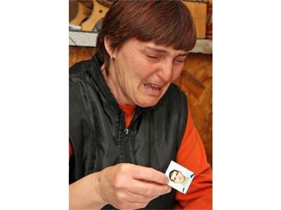 Майката на момчето Мая не може да скрие сълзите си, гледайки неговата снимка.