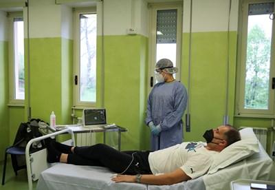 Медик проверява болен от коронавирус.  СНИМКА: РОЙТЕРС