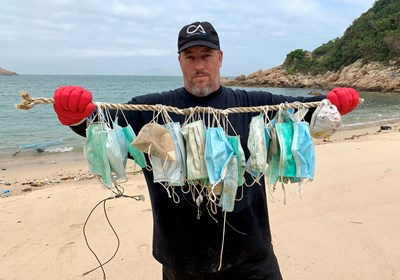Екоактивист показва десетки маски, които е събрал по замърсените плажове в Хонконг. СНИМКА: РОЙТЕРС