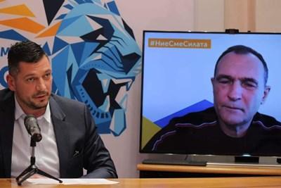 """Председателят на партията""""Българско лято""""  Борил Соколов пред екрана, на който Васил Божков се включи на живо от Дубай. СНИМКА: РУМЯНА ТОНЕВА"""