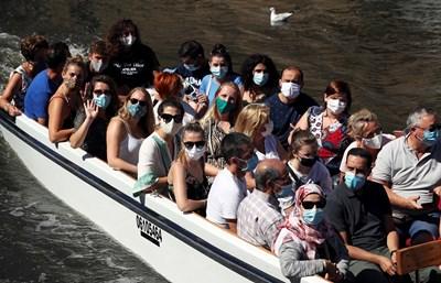 Белгийци носят защитни маски, докато се наслаждават на разходка с лодка по канал в Брюж.  СНИМКИ: РОЙТЕРС