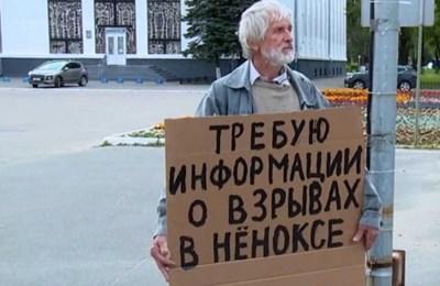 Възрастен мъж държи плакат, с който иска информация за инцидента на полигона край село Ньонокса.