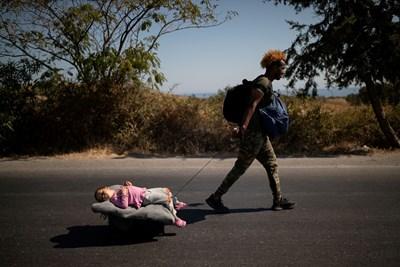 """Мигрантка напуска изпепеления лагер """"Мория"""" на гръцкия о. Лесбос. СНИМКА: РОЙТЕРС"""