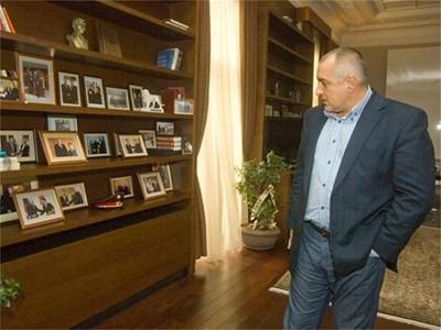 Борисов пред библиотеката в кабинета си. На лавиците са подредени много снимки от негови срещи с влиятелни световни личности. СНИМКИ: НИКОЛАЙ ЛИТОВ