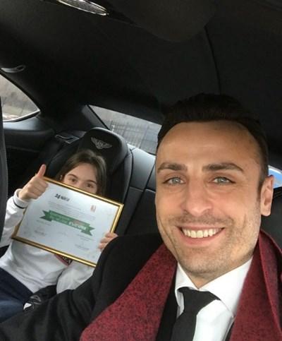 """Димитър Бербатов с широка усмивка, а на заден план една от двете му дъщери държи грамотата от """"Достойните българи""""."""