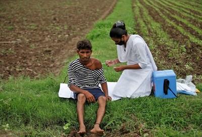 Медсестра ваксинира индийски селянин направо на полето.  СНИМКИ: РОЙТЕРС