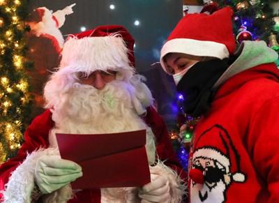 Дядо Коледа чете писмо на малко момченце с подаръците, които е поискало за празника. СНИМКА: РОЙТЕРС