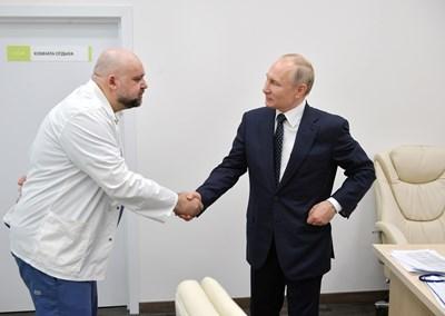 Руският президент Владимир Путин се ръкува с д-р Денис Проценко, шеф на болница край Москва, в която лекуват пациенти с коронавирус.