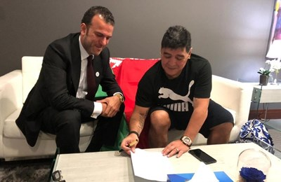 """Диего Марадона подписва в Дубай договора в присъствието на представител на """"Динамо"""" (Брест). Зад тях е знамето на Беларус."""