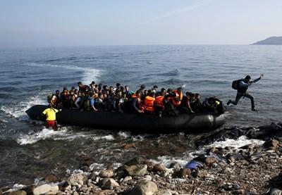 Мигрант скача от претъпкана надуваема лодка на бреговете на остров Лесбос. СНИМКА: РОЙТЕРС