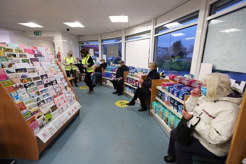Британци се редят на опашка в аптека с дистанция, за да бъдат ваксинирани.