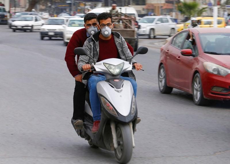 Мъже в Ирак управляват мотор с маски.