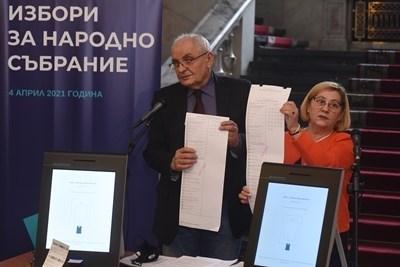 """Говорителите на ЦИК Димитър Димитров и Таня Цанева показват машините и бюлетините, с които се гласуваше на вота на 4 април. СНИМКА: """"24 ЧАСА"""""""