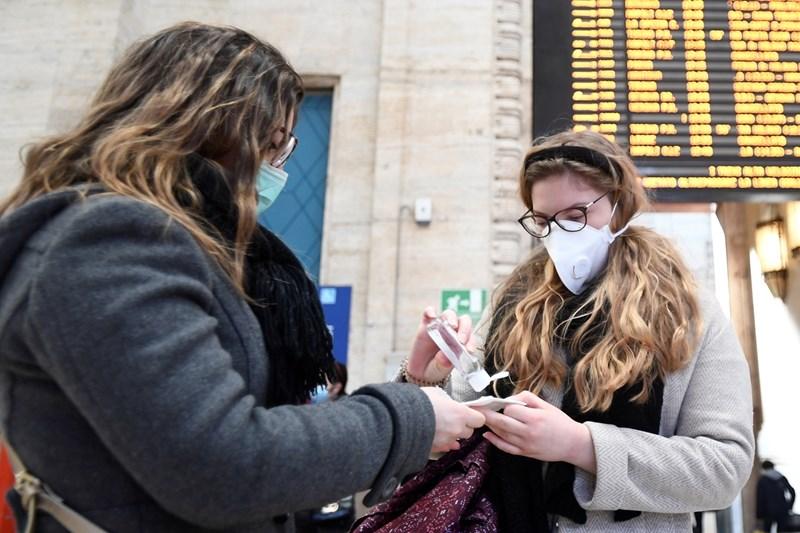 Хора дезинфекцират ръцете си на жп гара в Милано
