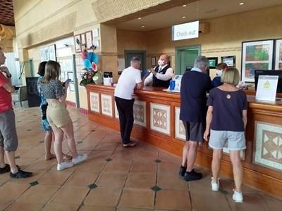 Служител на рецепцията с маска дава напътствия на гостите на блокирания хотел в Тенерифе.
