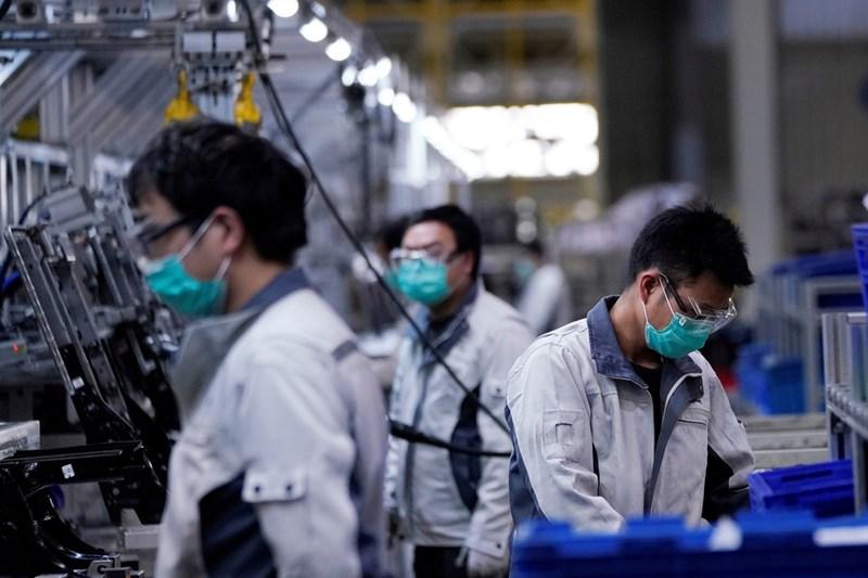 Работници с маски във фабрика в Шанхай