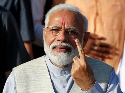 Индийският премиер Нарендра Мори показва пръста си, нацапан с мастило, след като гласува на третата фаза на парламентарните избори СНИМКИ: Ройтерс