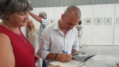 """Роденият през 1979 г. в Търговище художник Станислав Трифонов-Насимо дава поредния автограф върху книгата си """"Скицникът на Насимо"""". СНИМКА: Архив"""