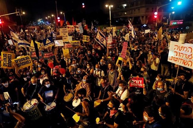 На оживен надлез северно от израелския търговски хъб Тел Авив демонстрантите развяваха черни знамена и скандираха лозунги, а преминаващи под тях автомобили надуваха клаксони.