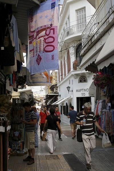 Туристи и местни се разхождат на битпазар в Атина, където е провесена хавлия с изрисувани 500 евро. СНИМКА: РОЙТЕРС